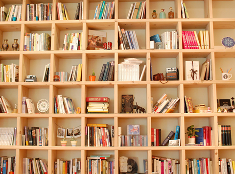 Square bookshelf with a variety of books and objects